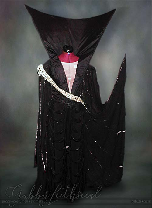 Front view of Dark Lily costume. Black fantasy dress with gold sash and a very tall collar.