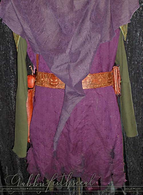 Back view of medieval green goblin costume on sewing form.