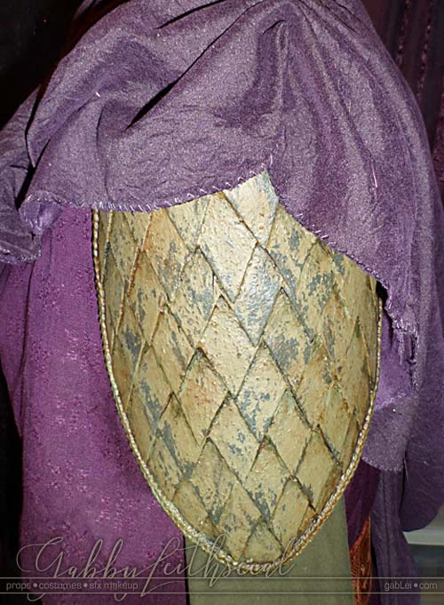 The green goblin costume scale armor pauldron against a purple tunic.