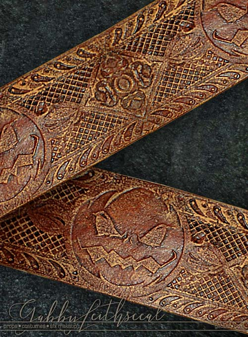 Close up of orange leather like belt with intricate pumpkin design for the green goblin costume.