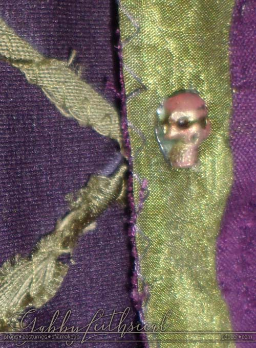 Close up skull buttons on the green goblin costume tunic.