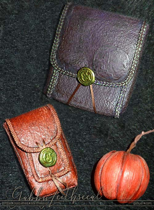 The Green Goblin costume purple leather like pouch with green trim, small orange leather like pouch and back of a pumpkin bomb .