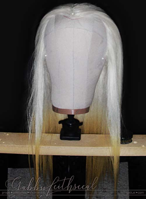 Front view of Prince Nuada costume's long, white to yellow gradient, hand laced wig on head form.