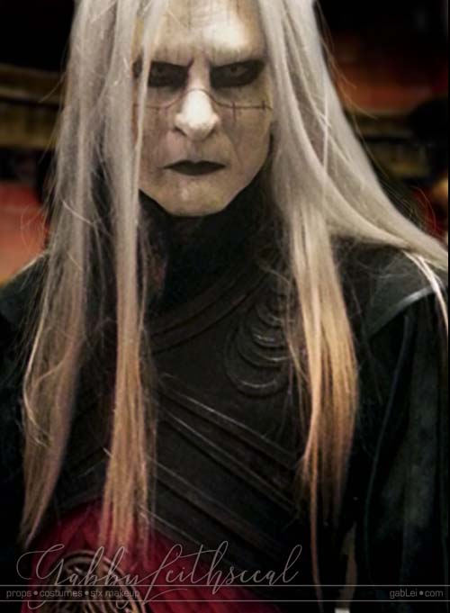 Closeup of woman wearing prosthetic mask, contacts, makeup, wig and costume of a crossplay of Prince Nuada.