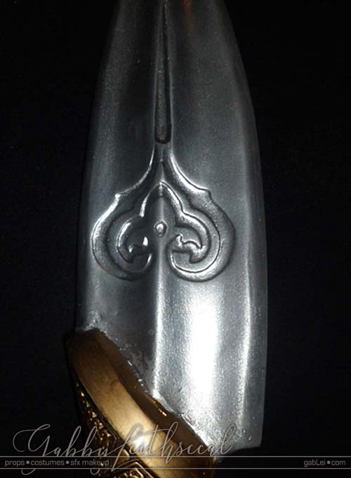Close up of finished, hand sculpted, large silver Prince Nuada spear with stylized engraved long heart detail.